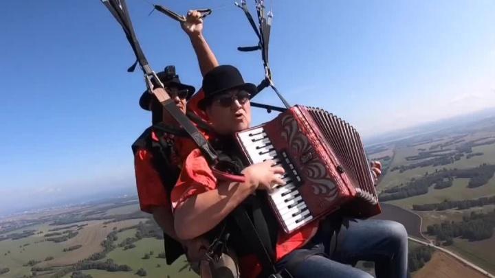 Новосибирский парапланерист поднял в небо аккордеониста для съёмок весёлого клипа