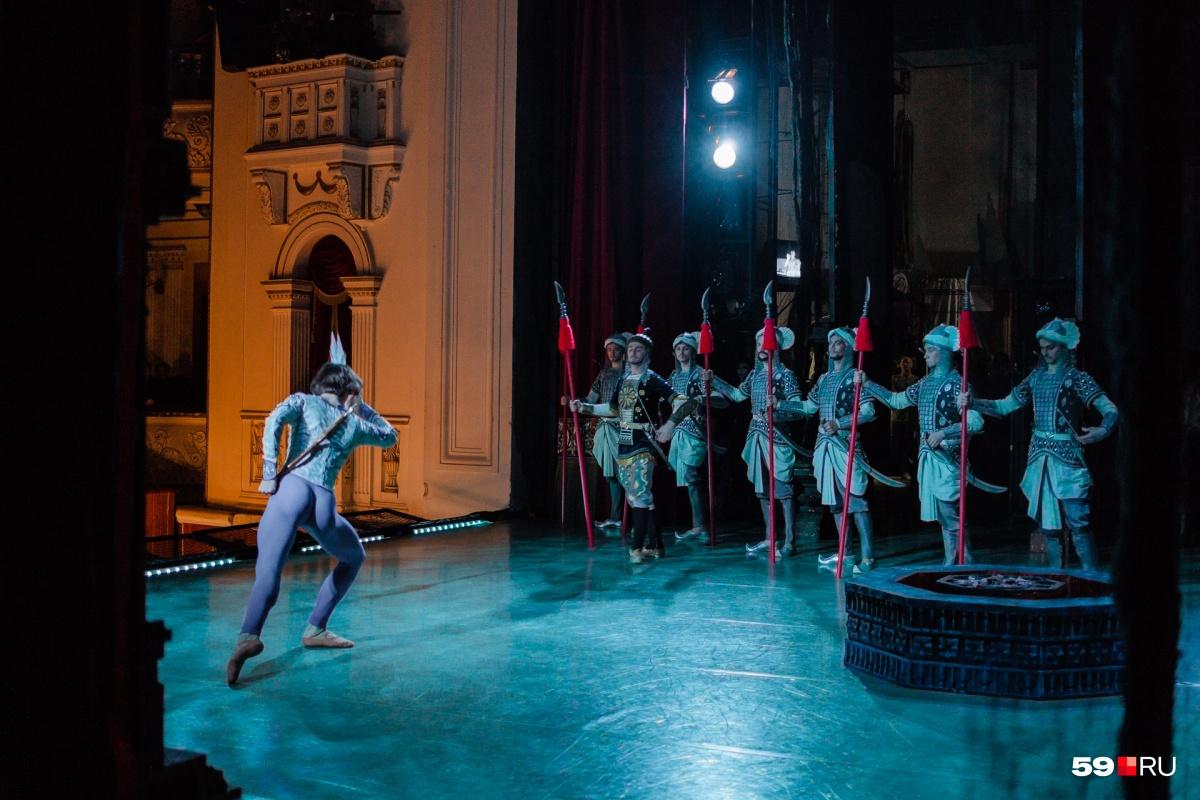 У каждого из артистов в этом балете — головной убор. Вид на сцену из-за кулис