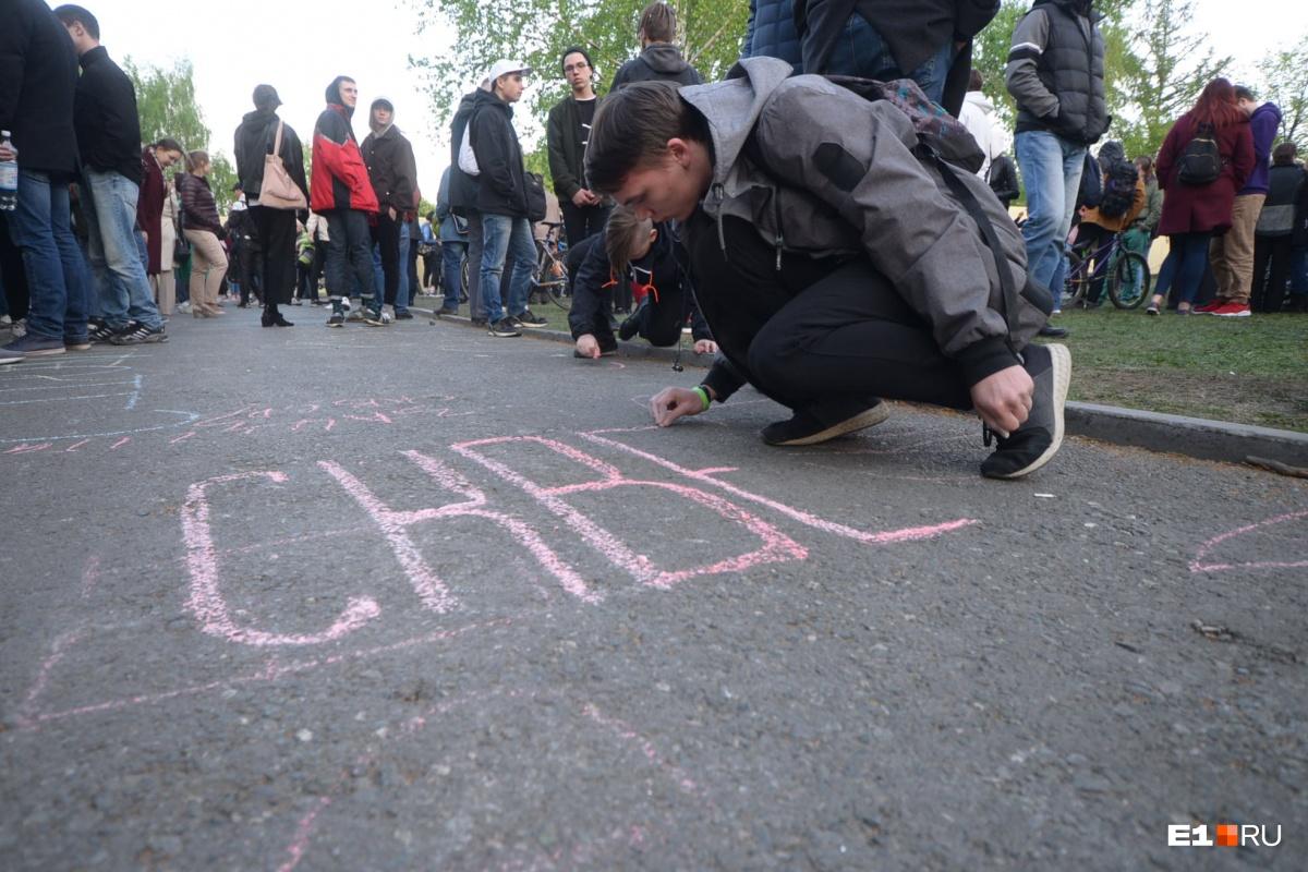 Жители города оставляют послания на асфальте в сквере во время акции протеста