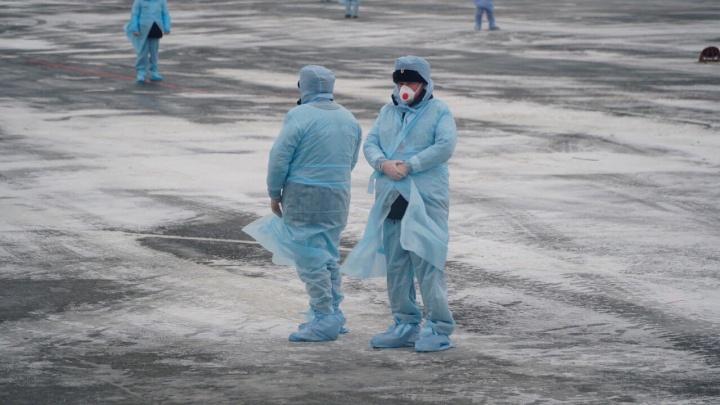 Костюмы химзащиты, одеяла и брезент под ногами: 15 кадров, как в Тюмени встретили пассажиров из Китая