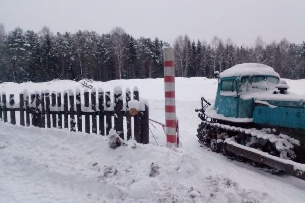 На въезде на полигон в Спирковской стоит трактор арендатора, мусоровозы проезжали через пространство рядом с ним<br>