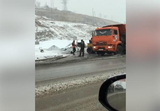 Дорожники уложили асфальт на дорогу в снежной каше и грязи