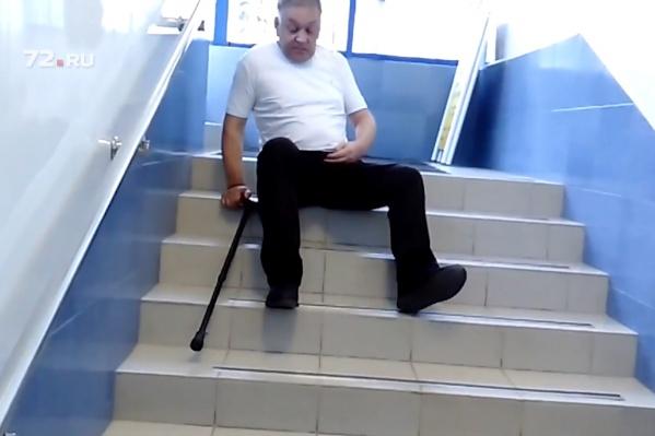 Чтобы подняться вверх по ступеням, мужчина садится и отталкивается ногой