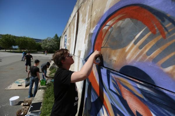 Граффитисты разрисовывают стену на Михайловской набережной