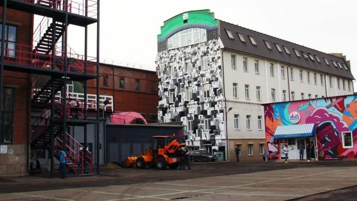 Екатеринбургский уличный художник нарисовал на здании завода серую толпу телефонов