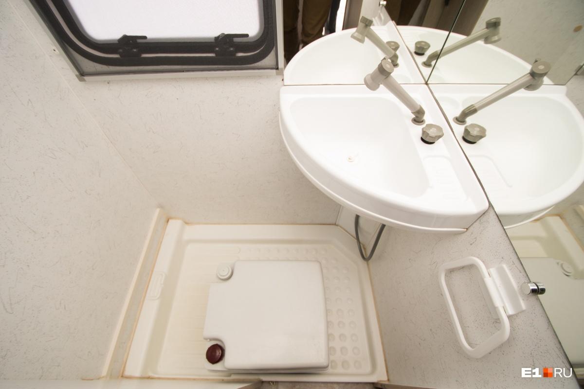 Душевая кабина с раковиной. На полу стоит переносной туалет