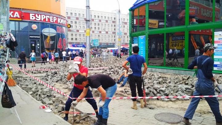 Рабочие оставили груду камней на месте тротуара на площади Маркса