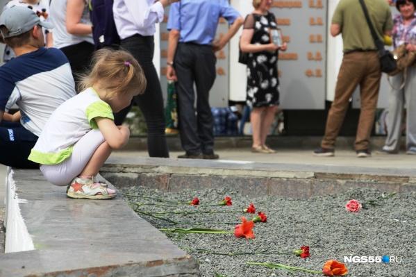 Девочка рассматривает цветы на мемориале бульвара Победы