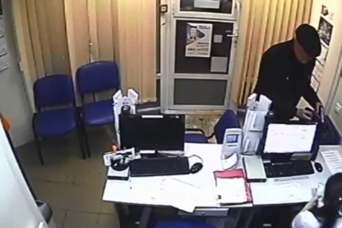На записи с камеры наблюдения слышно, как налётчик требует деньги и грозит работнику офиса словами: «Только попробуй нажать на кнопку»
