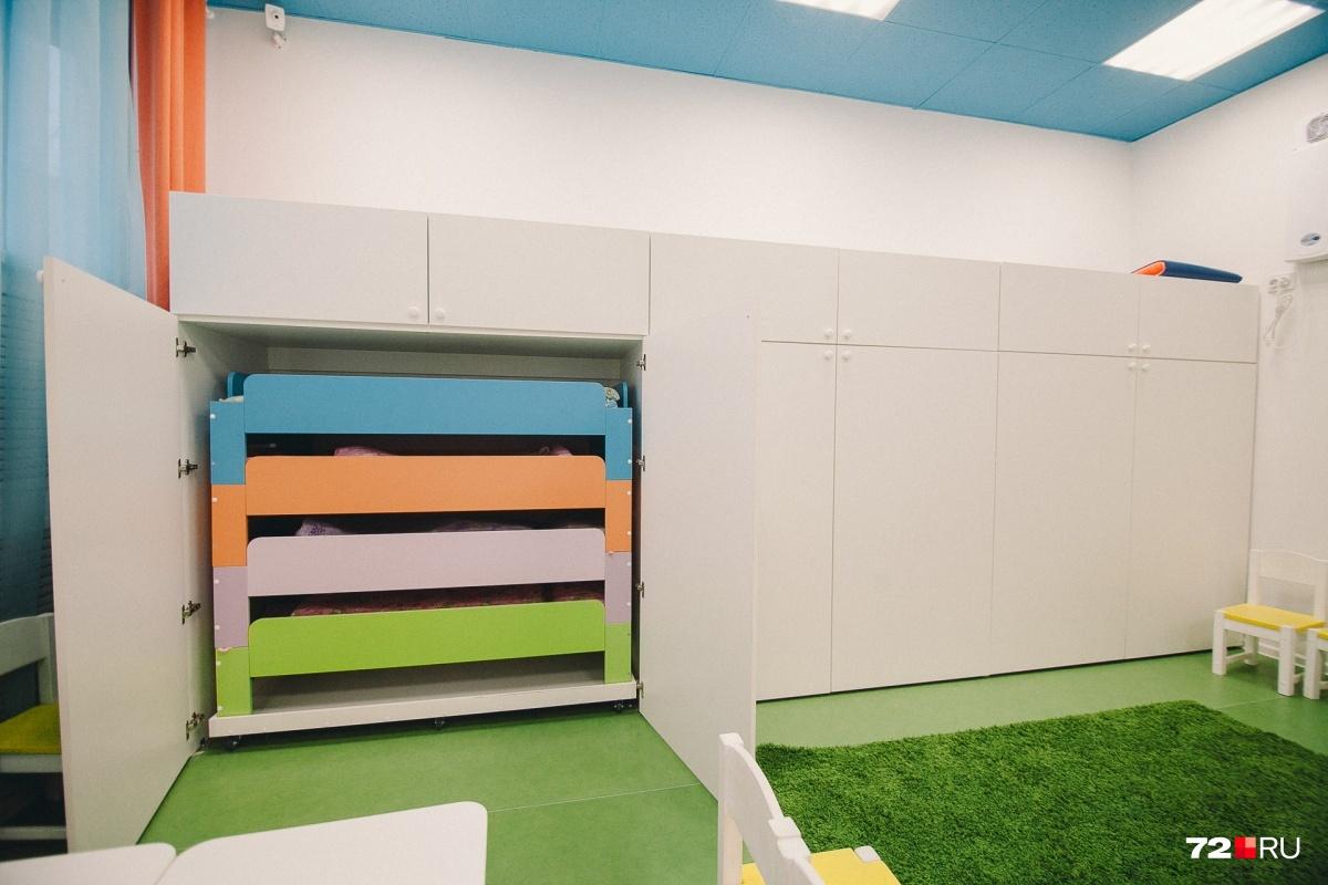 В стене прячутся кроватки. Когда приходит время сна, воспитатели достают их и расставляют по залу