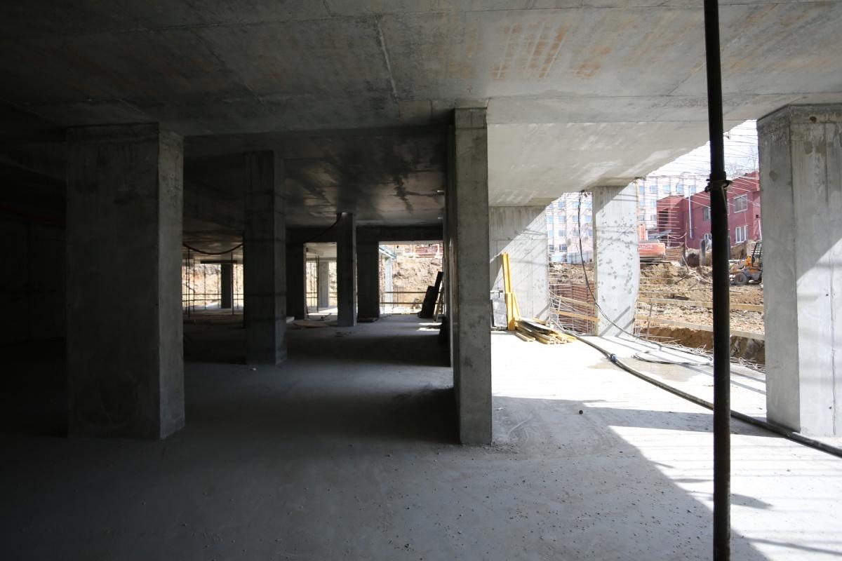 На стройке сейчас монтируют дренажную систему,укрепляют стены котлована, бетонируют фундаментную плиту ивертикальные конструкции