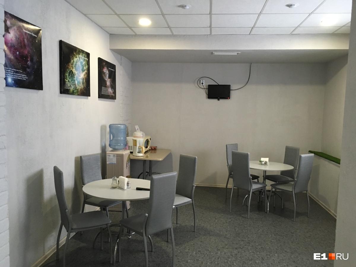 Это общая зона —«кухня». Два столика, кулер и микроволновка