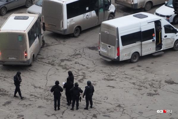На площадке, где собрались правоохранители, паркуются автобусы нескольких маршрутов