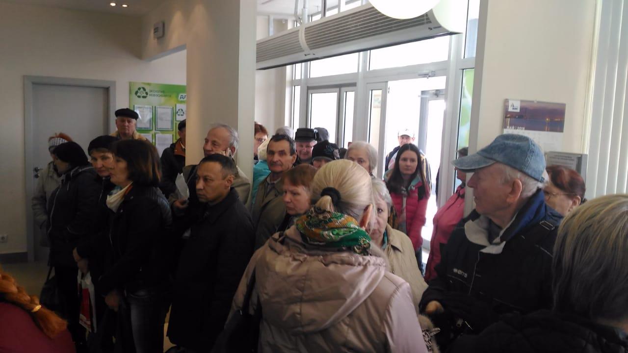 Люди стоят в очереди у входа
