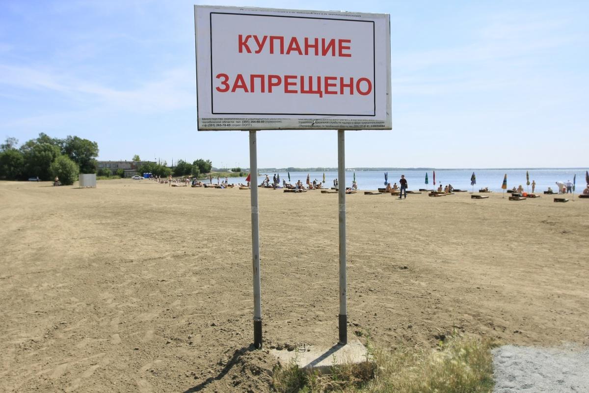 Плакат с надписью «Купание запрещено» не останавливает челябинцев, и они продолжают отдыхать на привычном пляже