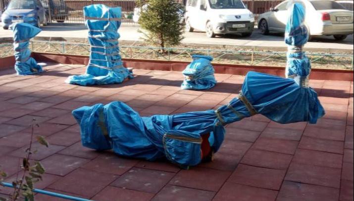 В новосибирском дворе качели и тренажёры замотали на зиму полиэтиленом. Угадайте зачем