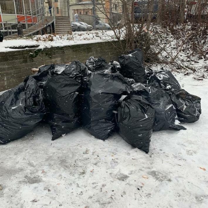 Мешки с отходами складывают у бетонного ограждения, где нет мусорной площадки