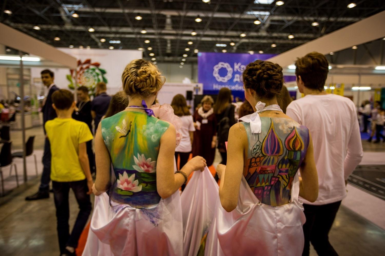 Аниматоры и наряженные девушки завлекают посетителей к своим стендам