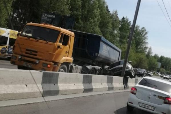 Внедорожник Infiniti застрял между отбойником и грузовиком