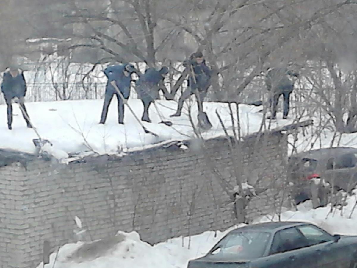 Школьники чистят снег на крыше сарая