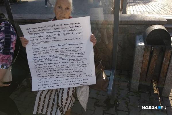 Женщина с плакатом сидит на остановке «Театр оперы и балета»