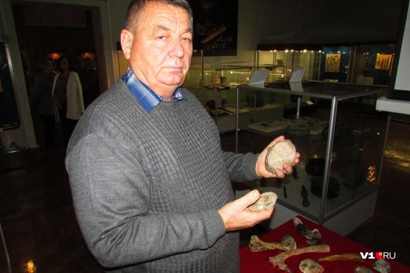 Александр Ярков держит в руках орудия древних людей