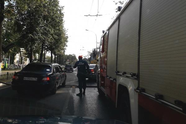 Спасатели тянут пожарный рукав через проспект
