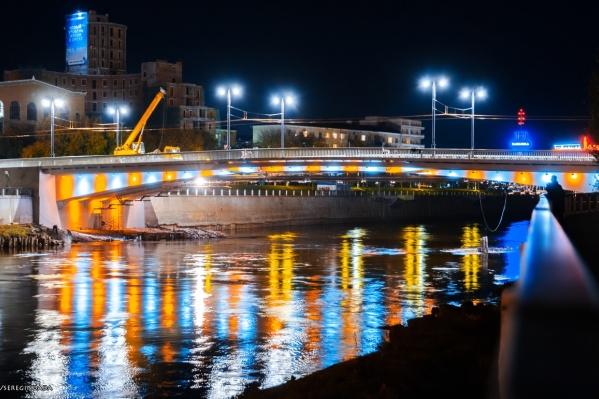 Подсветка моста красиво отражается в воде