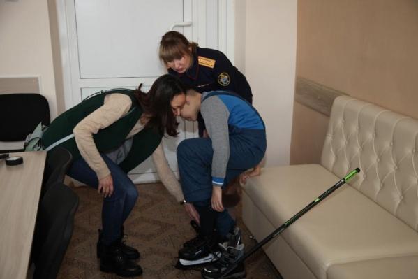 Ребёнок с мамой и руководителем пресс-службы СУ СКР по Омской области примеряет новые коньки