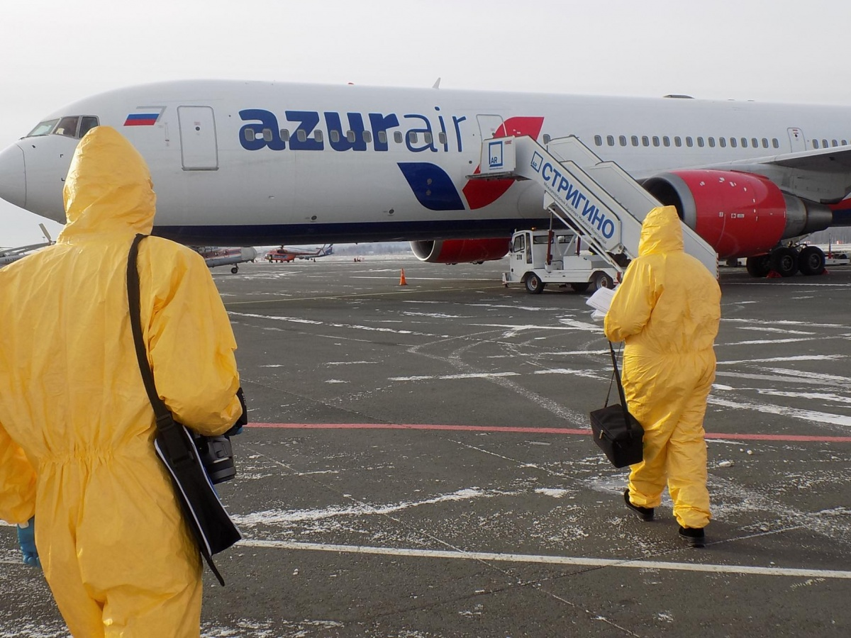 Сотрудники Роспотребнадзора направляются на борт самолёта, чтобы проверить туристов тепловизором
