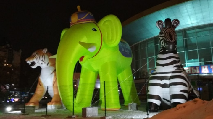 Возле цирка поставили огромного зелёного слона и тигра с зеброй