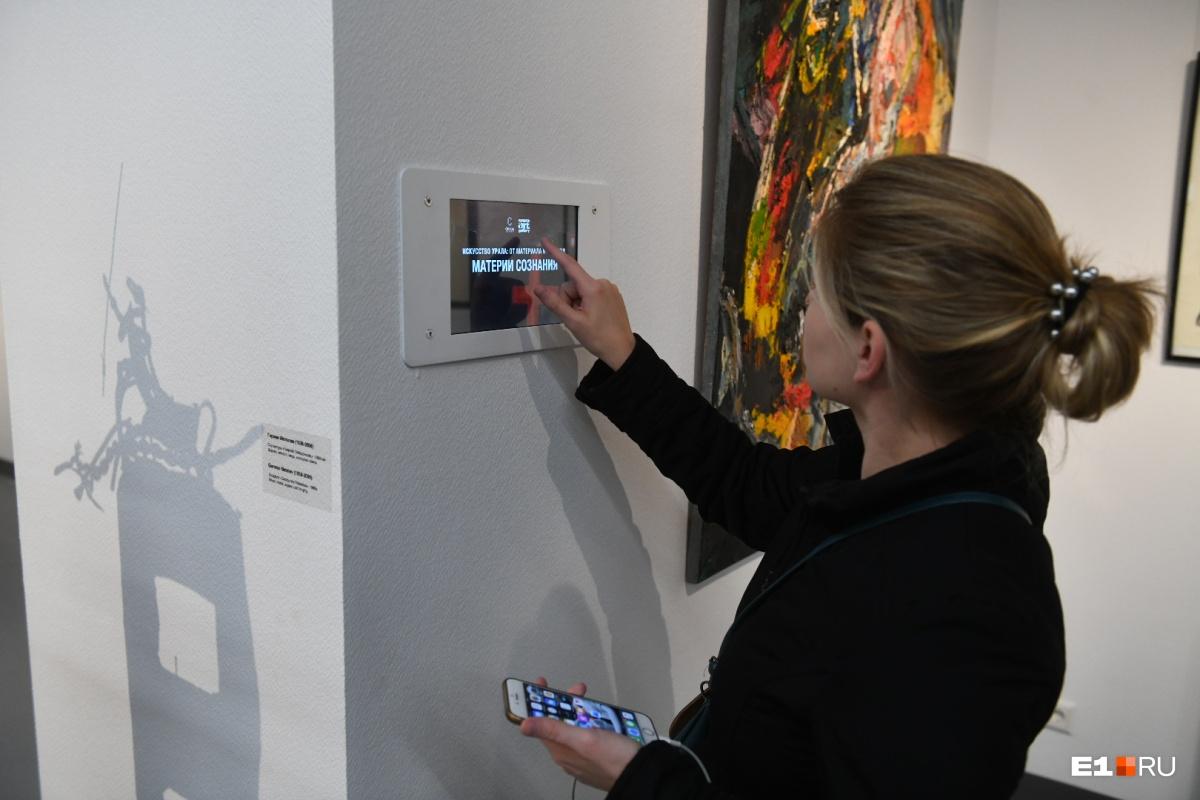 Зал современный, с планшетами для получения информации о выставке и экспонатах