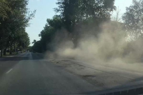 За трактором, который подметал тротуар, тянулись клубы пыли