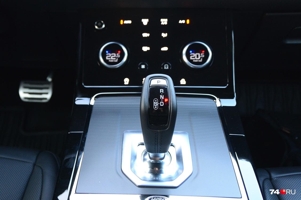 Селектор девятиступенчатого автомата работает по «немецкому» алгоритму: нажимаешь курок разблокировки и качаешь. Вперёд — задний ход, назад — режим D, влево — спортивный. Сверху кнопка режима «паркинг»