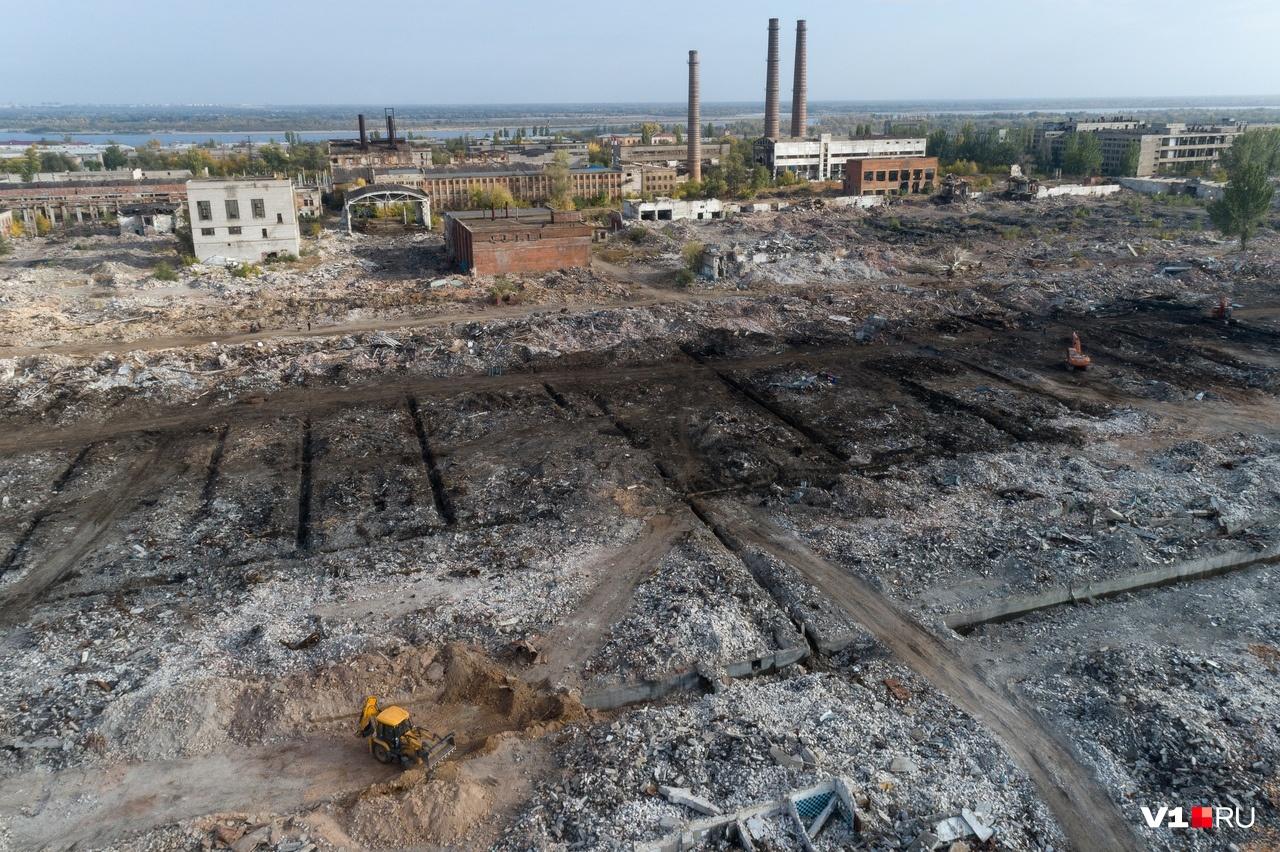 Солидный трактор выглядит муравьишкой на фоне разрушенного завода