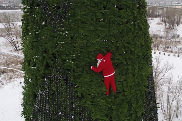 Монтажника нарядили в костюм Санты и подняли на ёлку строительным краном