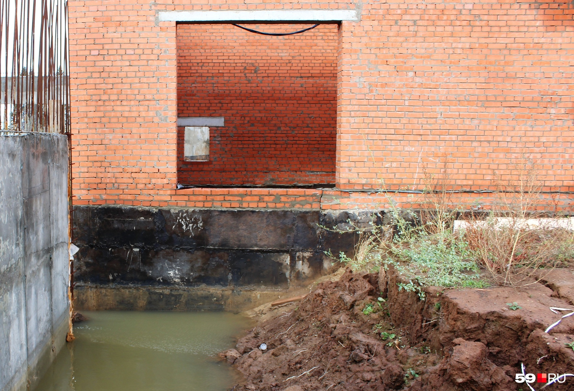 На кирпичной стене над фундаментом видна трещина