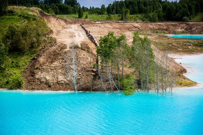 В разных частях золоотвала вода имеет разный оттенок— возле берега она прозрачная, а где-то почти бирюзовая