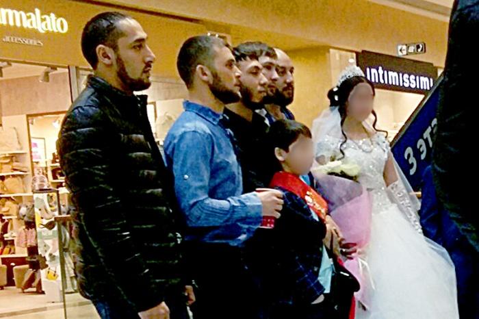 Юные жених и невеста в окружении многочисленных родственников