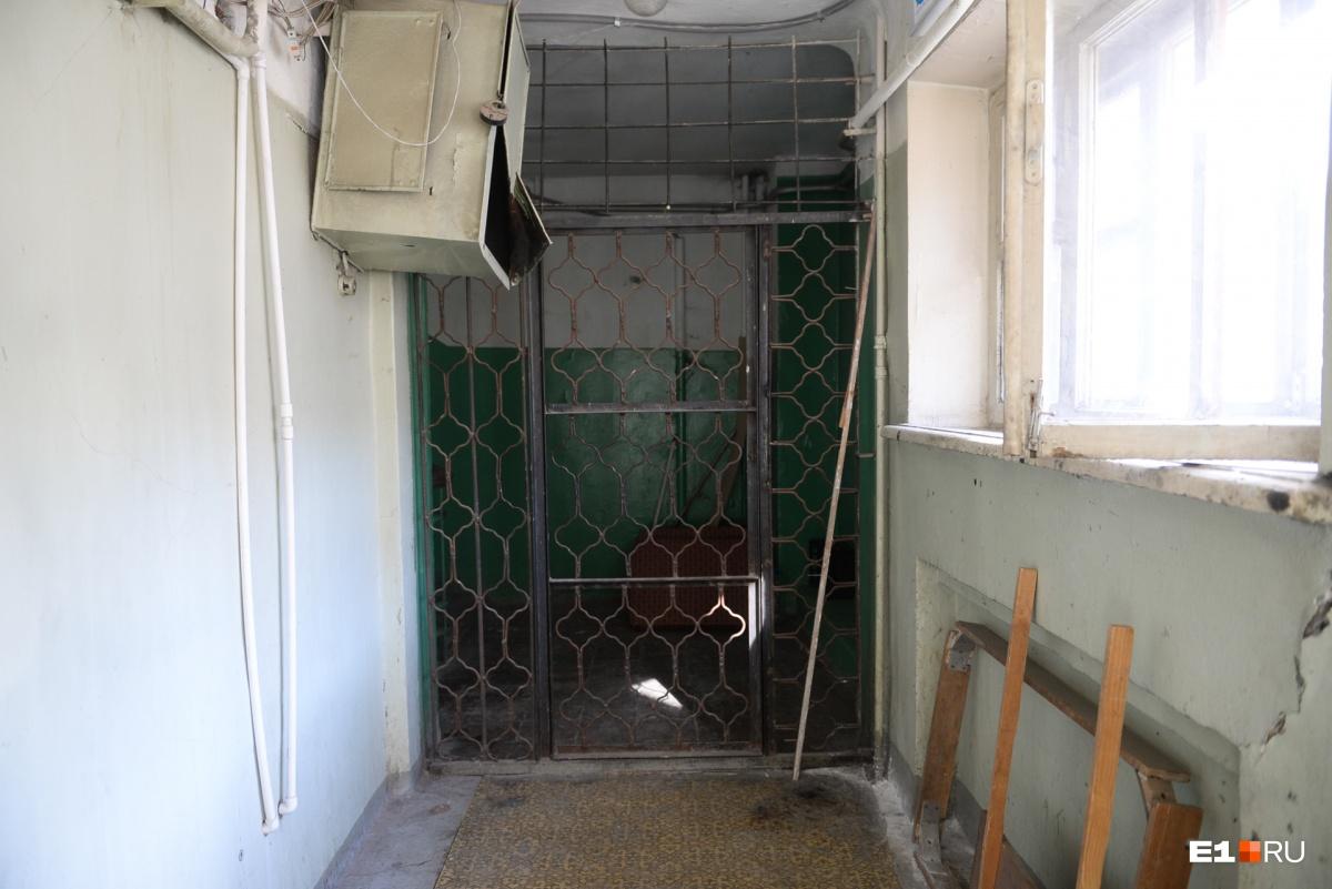В конце коридора — решетка. За ней — переход в другой корпус. Но дверь закрыта