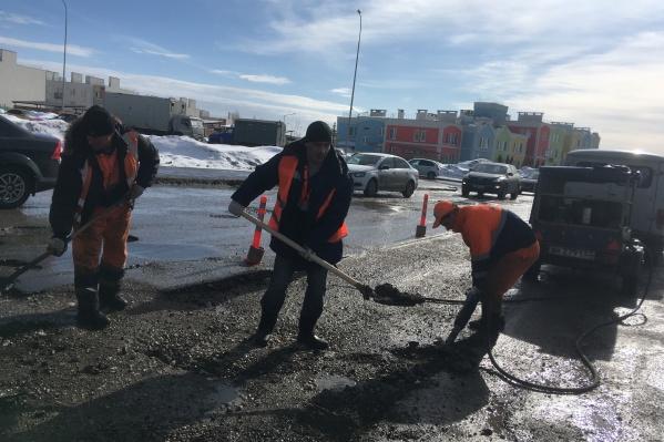 Рабочие заделали ямы литым асфальтобетоном