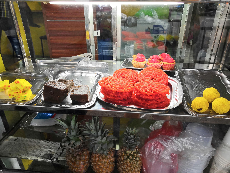 Витрина в небольшом магазинчике. Тут свежие фрукты соседствуют с пирожными и пастилой