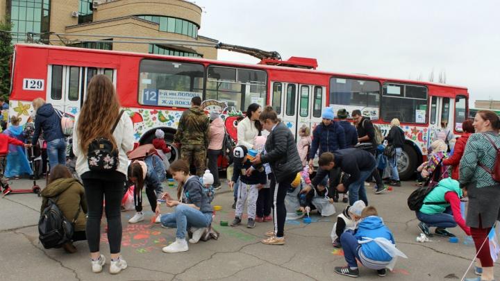 Сотни омских детей за 20 минут раскрасили четыре троллейбуса и асфальт под ними