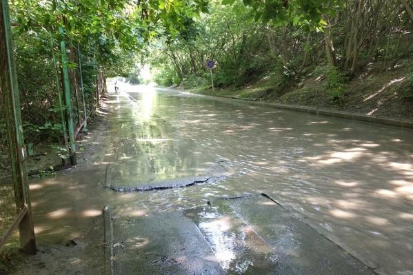 Горячая вода, которой залило дорогу, мощным потоком вытекает из трубы под Коммунальным мостом