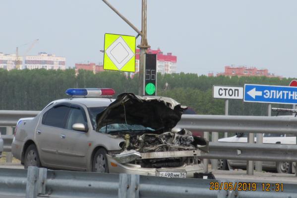От столкновения у Nissan смяло капот и бампер. Проблесковые маячки на крыше Nissan на самом деле принадлежат полицейской машине, стоящей на заднем плане