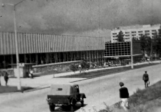 Судя по одежде и автомобилям, перед нами 1960-е. На скриншоте — ТЦ Академгородка, который открылся в 1962 году