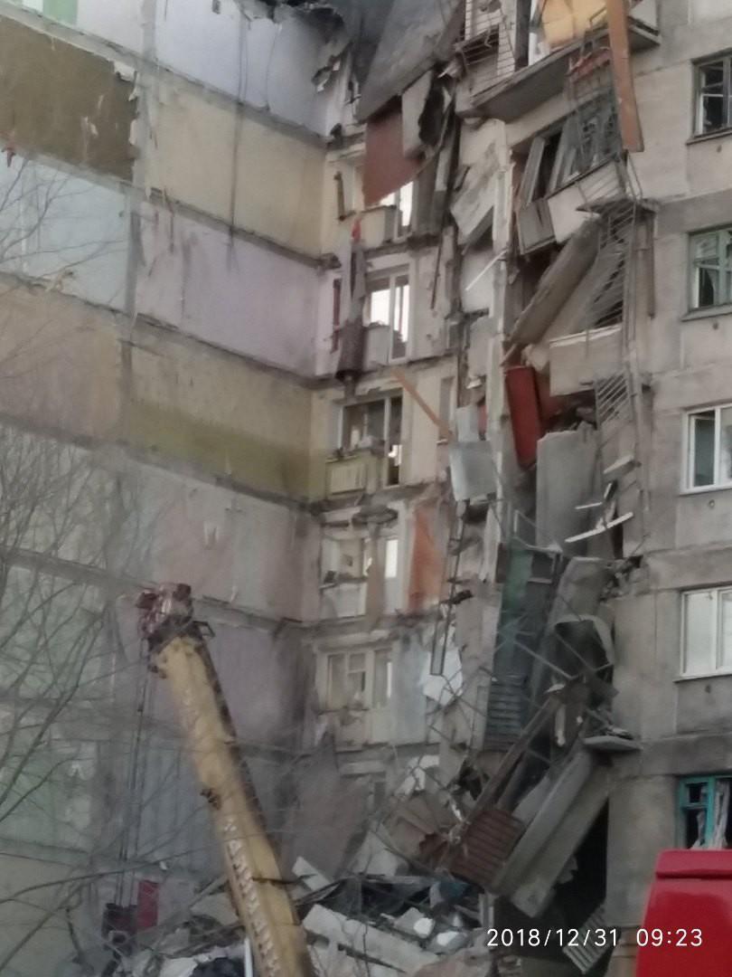 Спасатели работают под висящей стеной, которая тоже может обрушиться