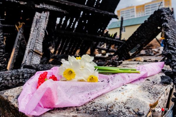 К сгоревшей конюшне приносят цветы