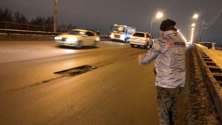 «Он опасен для жизни»: общественники насчитали 40 поврежденных машин на Октябрьском мосту