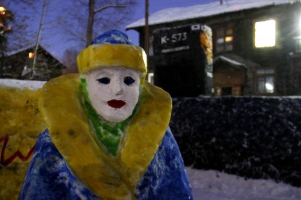 Фигура на переднем плане — судя по всему, Снегурочка. Вместе с подводной лодкой на фоне деревянного барака она выглядит не так уж и странно